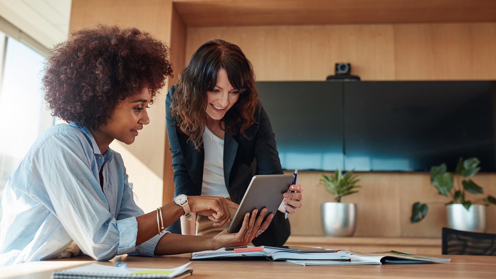 Foto de duas mulheres olhando para um tablet