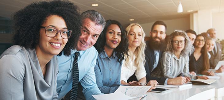 Foto de várias pessoas alinhadas em um ambiente corporativ