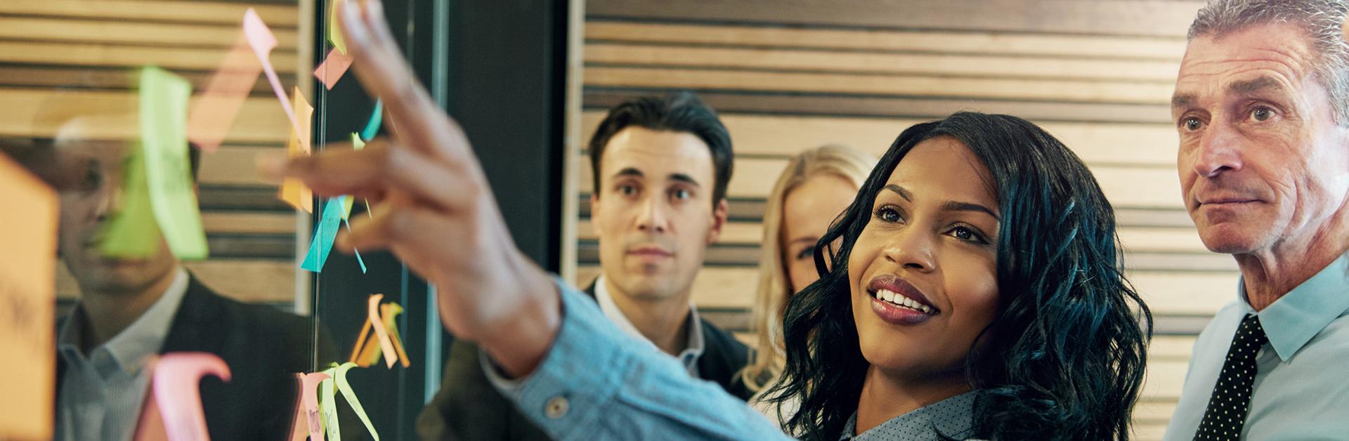 Foto de uma mulher colando post-its em uma reunião.
