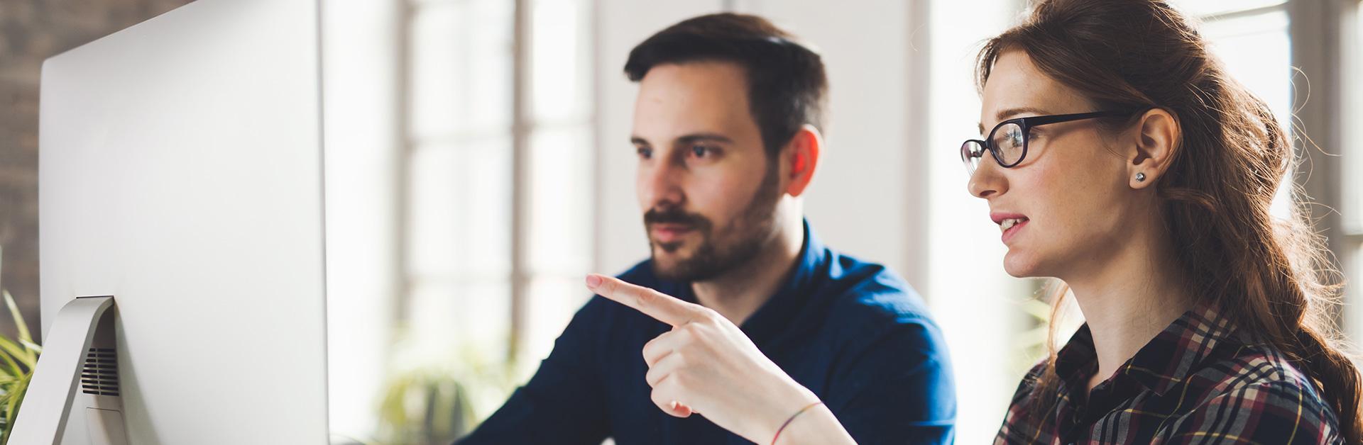 Foto de um homem e uma mulher olhando para o computador