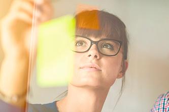 Foto de uma mulher colando post-its em um vidro