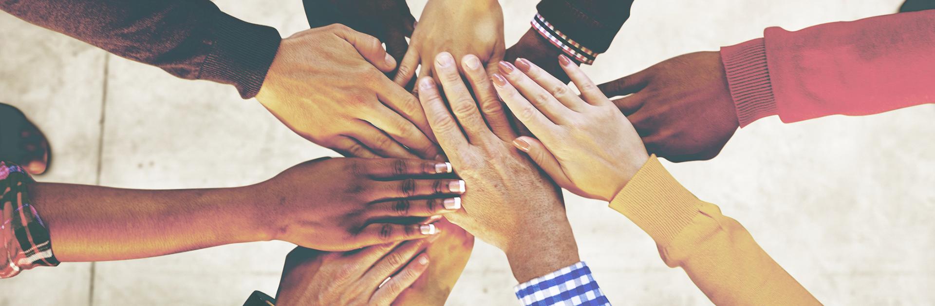 Foto de várias mãos de pessoas de diversas etnias, uma sobre a outra