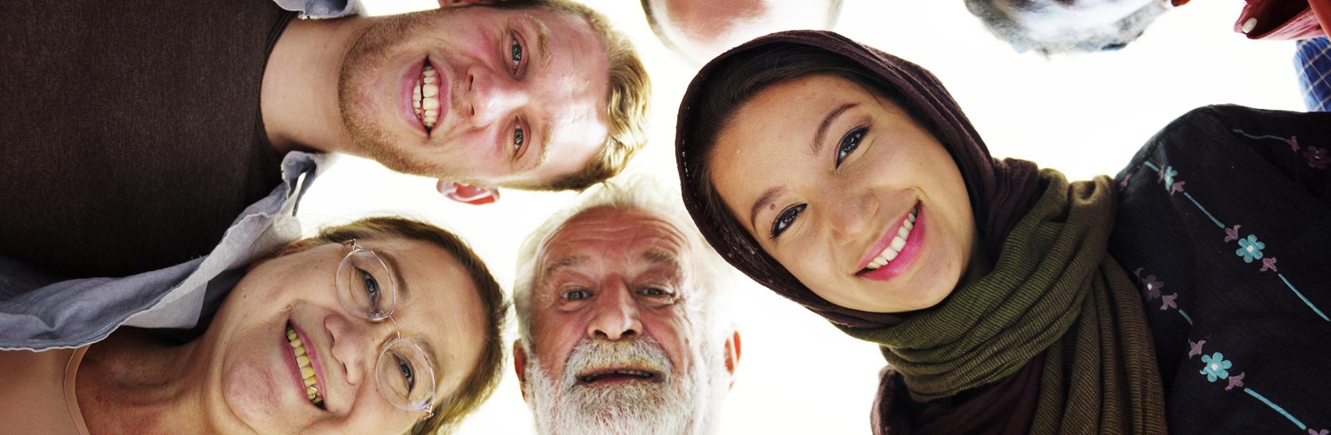Foto de quatro pessoas olhando para baixo, uma mulher usa um véu sobre a cabeça, uma mulher é mais velha de óculos, um homem tem barba branca e um homem é jovem