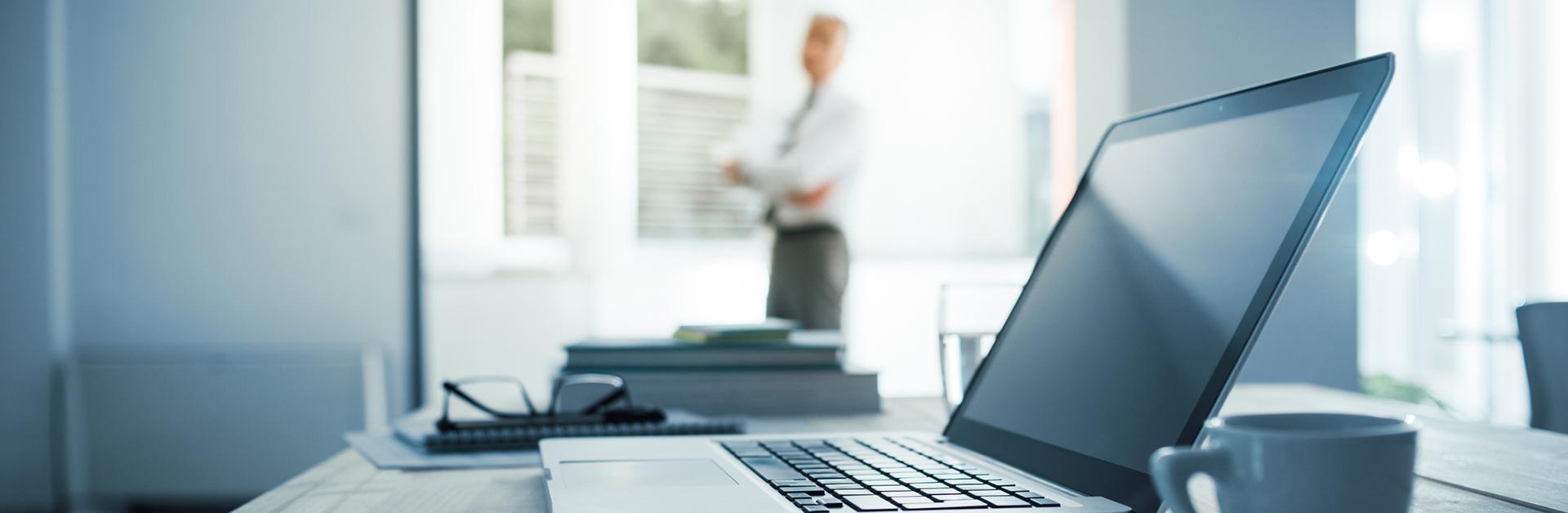 Foto de um homem em um escritório com foco no computador.