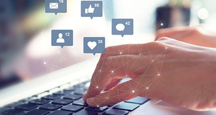 Foto de duas mãos sobre o teclado do computador, cobertas por ícones de redes sociais