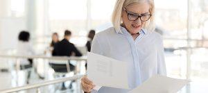 Mulher com cara de preocupada olhando para folhas de papel