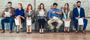 Foto de sete pessoas sentadas em uma sala de espera com papéis nas mãos, um dos homens olha par ao relógio.