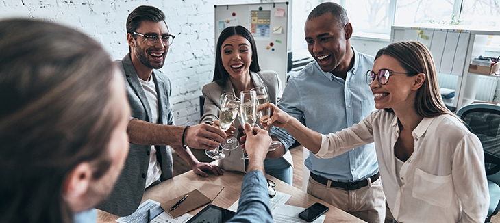 Foto de cinco pessoas com roupas sociais brindando com copos de champanhe