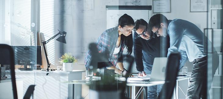Foto de três homens sobre uma mesa de trabalho