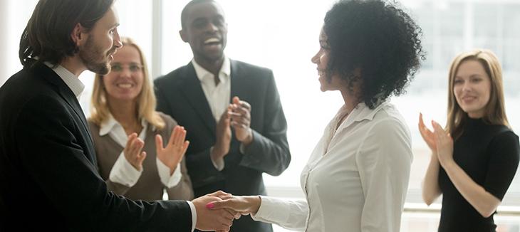 Foto de duas pessoas apertando as mãos enquanto outras três batem palmas