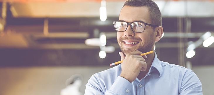 Foto de um homem pensando com um lápis na mão