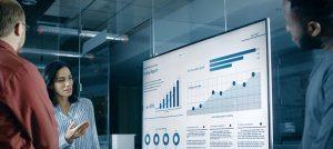 Foto de três pessoas olhando para gráficos no monitor