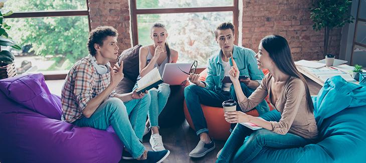 Foto de quatro pessoas conversando sentadas em pufes