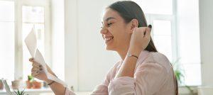 Foto de uma mulher sorrindo ao ler um papel.