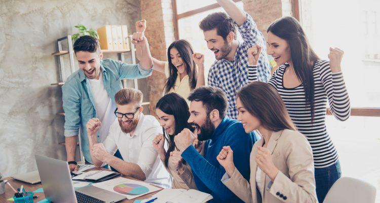 Time de executivos comemorando os resultados que observam num computador.