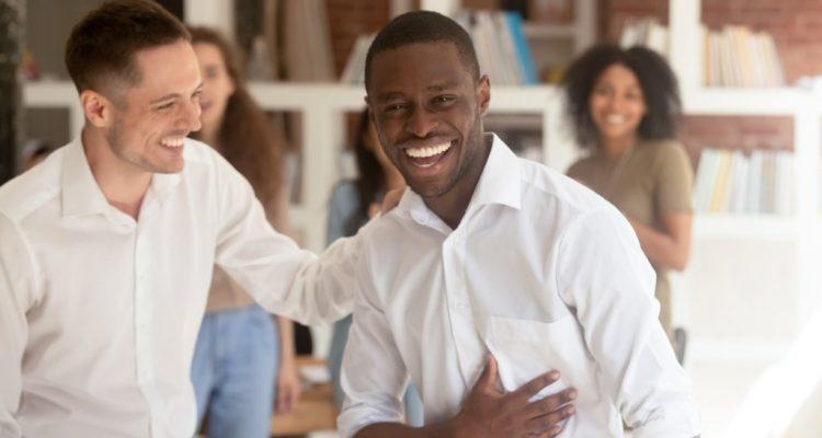 Executivo de sucesso rindo ao lado de um colega de trabalho.