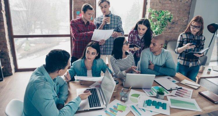 Jovens executivos debatem numa sala planilhas e números de uma organização.