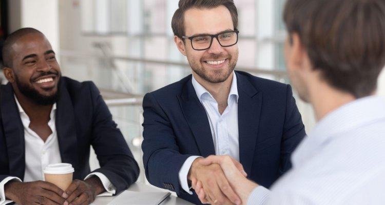 Dois executivos selam um acordo com aperto de mãos, ao lado um terceiro executivo observa com felicidade a cena