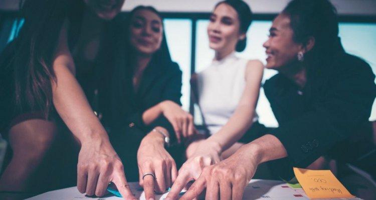 Executivas fazem um brainstorm com post-its em cima de uma mesa com cronogramas.