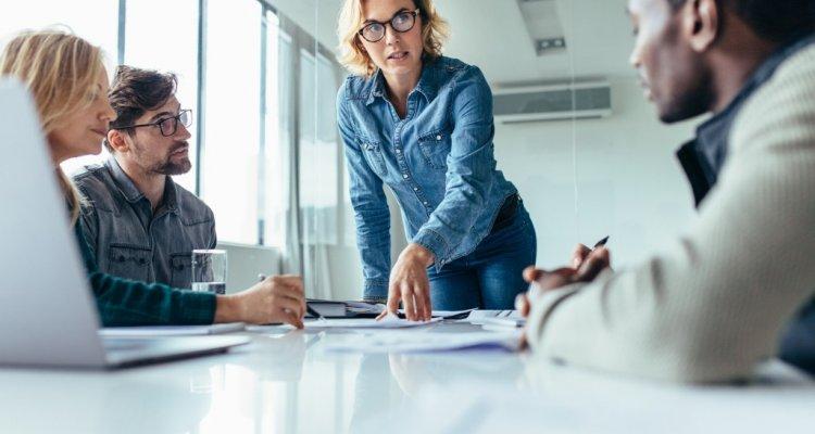 Mulher líder fala sobre indicadores com a equipe.