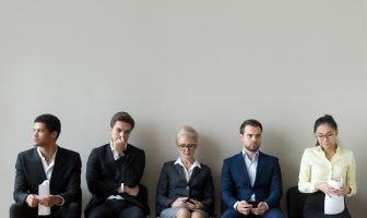 Candidatos sentados em cadeiras esperam ansiosos pela entrevista de emprego.