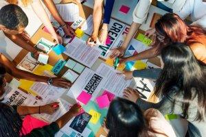 Funcionários debruçados em cima de uma mesa analisando planos estratégicos e criativos.