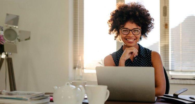 Executiva com óculos à frente de um computador sorrindo.