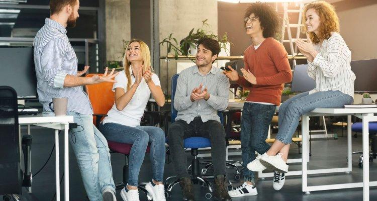 Numa reunião de equipe, jovens executivos aplaudem um colega de trabalho.