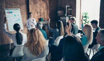Executivos sentados numa sala de aula in company levantam à mão para questionar a treinadora.