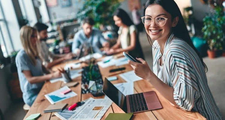 Executiva com óculos segura o celular na mão e a sua frente tem notebook, ao lado colegas de trabalho se reúnem.