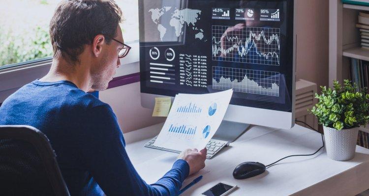 Um executivo sentado à sua mesa de trabalho observando um dashboard no papel e no monitor de seu computador