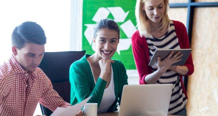 colegas de trabalhos reunidos numa mesa ao fundo o simbolo da reciclagem pendurado numa parede