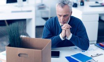 executivo experiente debruçado à mesa de trabalho com um olhar pensativo, a sua frente uma caixa de papelão com uma planta dentro