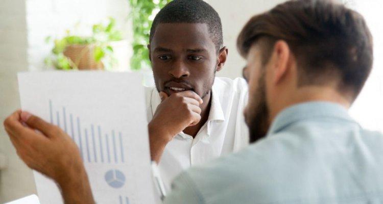Executivo negro observando dados num papel que está sendo segurado por outro executivo.