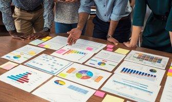 Executivos se debruçam numa mesa de trabalho para analisar dashboards