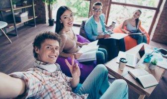 Jovens executivos reunidos no escritório fazendo uma selfie.