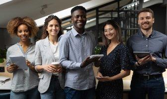 Executivos diversos reunidos à frente de uma mesa de trabalho sorriem