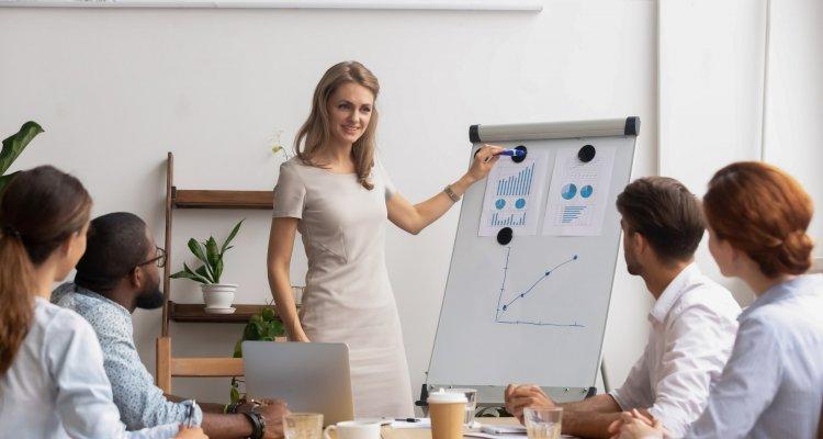 executiva explica números de um dashboard exposto num quadro aos colegas reunidos na mesa