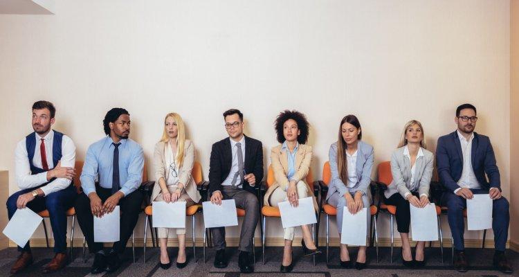 candidatos a emprego com feições tensas sentados numa fila de cadeiras segurando seus currículos