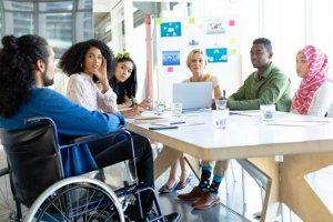 Diversidade na empresa representada por pessoas de todas as etnias em uma reunião.