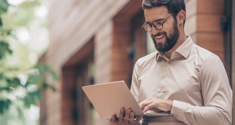 Homem rindo ao visualizar a tela do notebook.