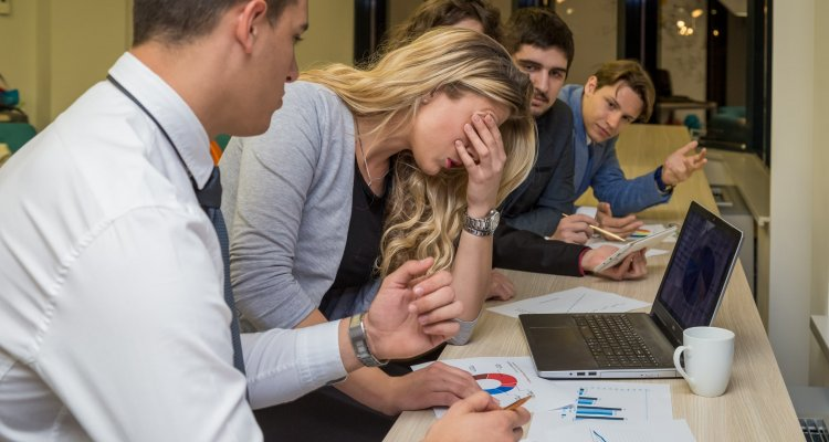 mulher ao centro da foto com a mão ao rosto, enquanto homens à pressionam por resultados