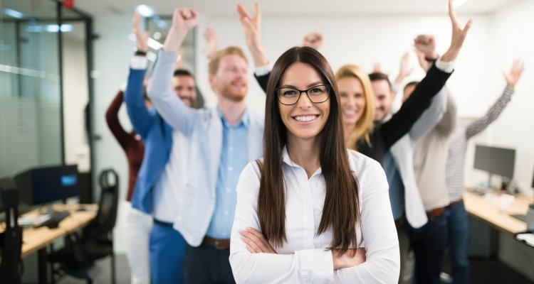 Liderança feminina de braços cruzados, ao fundo colegas de trabalho levantam o braço