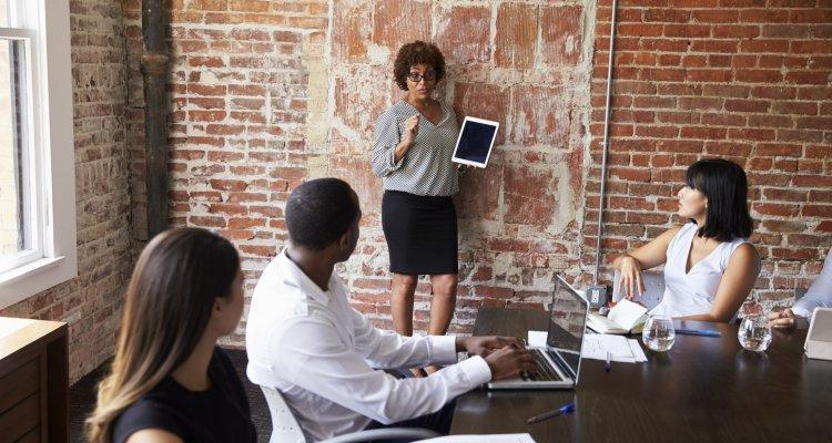 Executiva está levantada à frente de seus colegas numa reunião segurando um tablet
