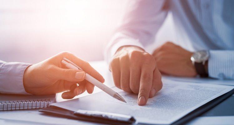 Executivos abordam questões técnicas de um contrato, apontando com o dedo e com uma caneta parte do texto do documento