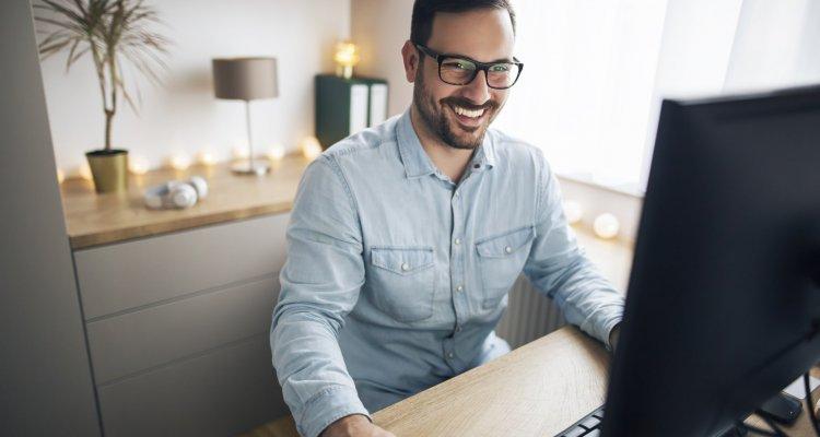 Executivo trabalha remotamente de sua casa em frente a um computador