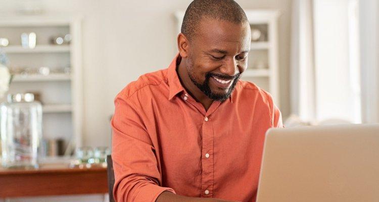 executivo negro está trabalhando remotamente à frente do computador na sua casa