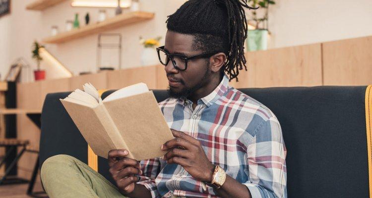 jovem negro sentado ao sofá lendo um livro