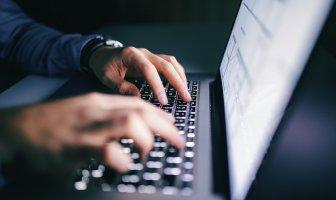 Mãos de um executivo digitando num laptop