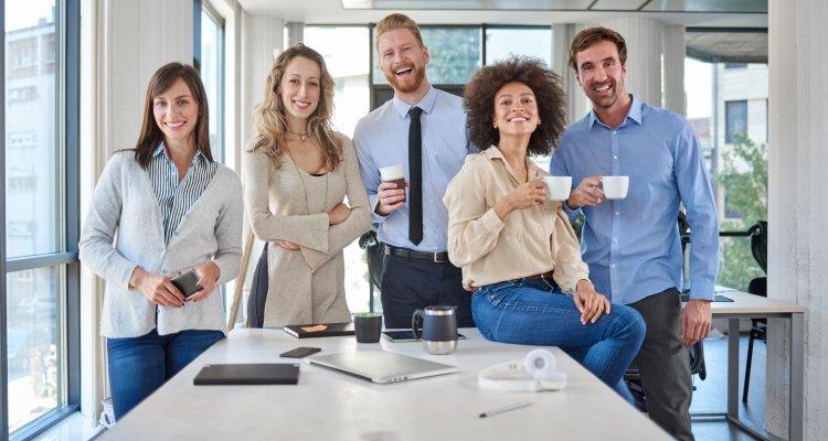 Equipe unida sorrindo em pé na beira da mesa
